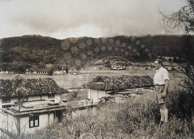 Dr. Curry, The Scots, M.O. in charge of the colony looks over a portion of the colony from the hill. Directly behind him is a portion of the residential area and over to the left are the hospital and administrative buildings. Just below the hill where Dr. Curry is standing are houses of some of the staff.
