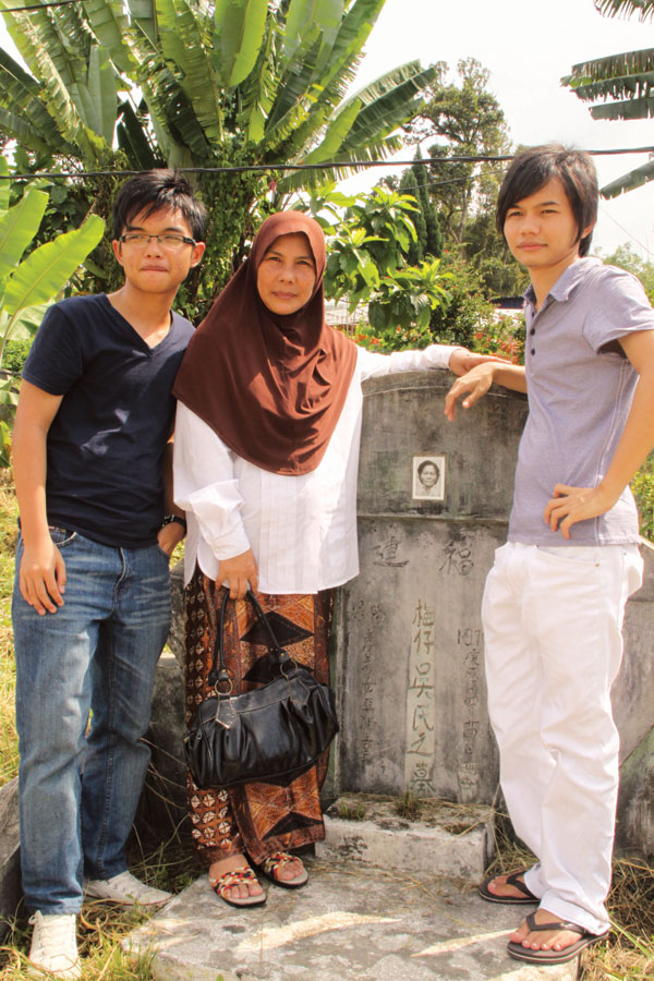 Noraeni and her sons in front of her biological mother's  grave.