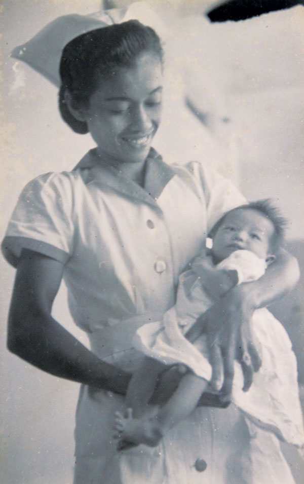 A nurse carrying Tan Cheng Hoe's infant daughter.